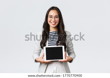 portrait of a businesswoman showing a digital tablet and smiling stock photo © imagedb