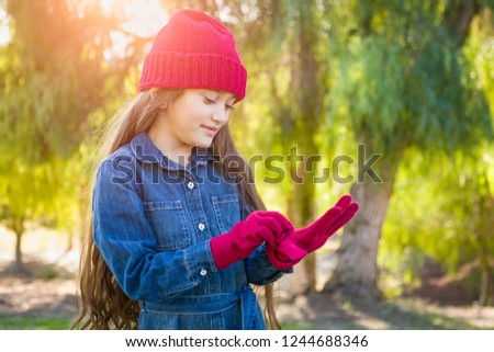 Cute Mixed Race Young Girl Wearing Red Knit Cap Putting On Mitte Stock photo © feverpitch