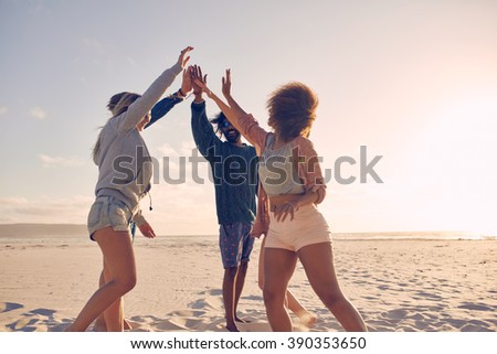 happy friends stacking hands on summer beach Stock photo © dolgachov