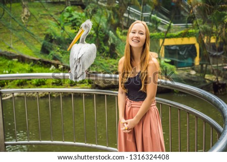 a young woman is photographed with a pelican great white pelica stock photo © galitskaya
