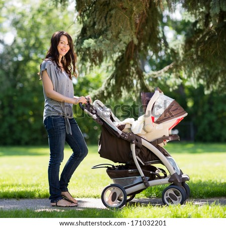 Portrait of beautiful young woman pushing baby carriage in the park Stock photo © Lopolo