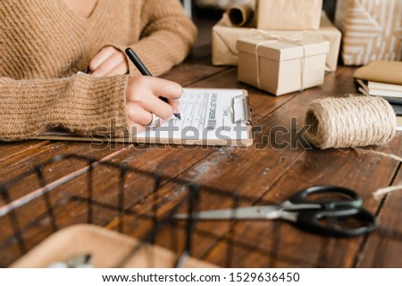 Young woman putting ticks by ordered goods in checklist by wooden table Stock photo © pressmaster