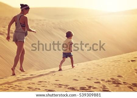 Fit mother with son running at the desert in Gran Canaria, Maspalomas on sunset Stock photo © galitskaya
