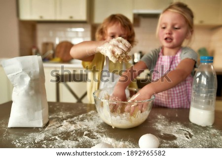 Female hands on those of little boy kneading dough for pastry on kitchen table Stock photo © pressmaster