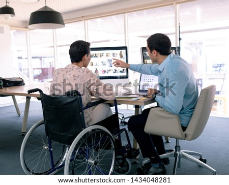 Rear view of disabled young mixed-race female executive interacting with handsome young Caucasian bu Stock photo © wavebreak_media