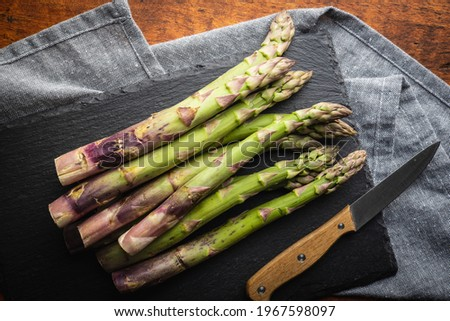 Fresh raw garden asparagus and knife closeup on cutting board on Stock photo © marylooo