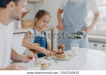 Unrecognizable mommy brings delicious pancakes to table, prepares breakfast for family. Cheerful gir Stock photo © vkstudio