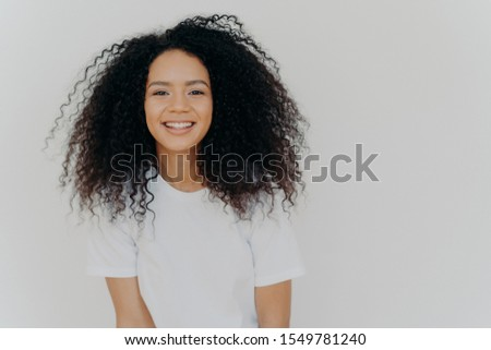Headshot of smiling woman has bushy luminous hair, stands confident and pleased, minimal makeup, enj Stock photo © vkstudio