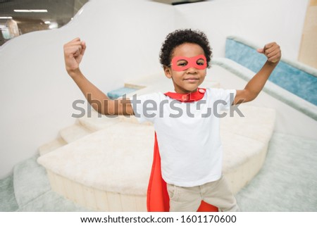 Cute little African boy in red mantle of super hero and white casualwear Stock photo © pressmaster