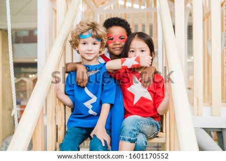 Three affectionate little friends in costumes playing on staircase together Stock photo © pressmaster