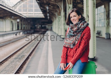 Glad young European woman wears red sweater, scarf, holds mobile phone, sits at bag, enjoy travellin Stock photo © vkstudio