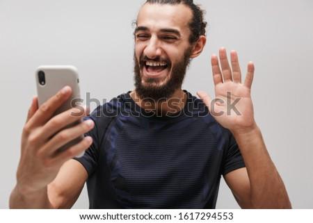Image of bearded joyful sportsman smiling while talking on smart Stock photo © deandrobot