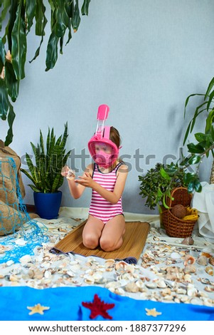 Little girl wearing snorkeling mask imitates swimming in fictional beach Stock photo © Illia