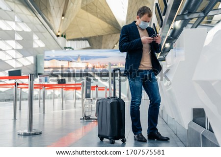 Man with luggage, wears medical protection mask, poses in airport terminal, travels by airplane duri Stock photo © vkstudio