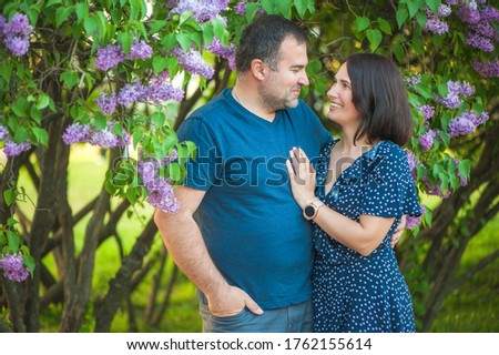 Beautiful couple in love is hugging near a lilac bush. lifestyle photo Stock photo © ruslanshramko