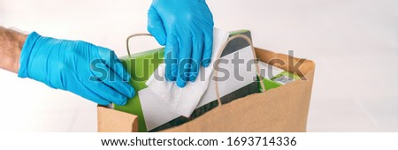 Coronavirus wiping down grocery packages after receiving home delivery wearing gloves, using disinfe Stock photo © Maridav