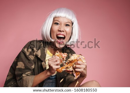 Image of wild asian girl screaming and tearing big burger apart Stock photo © deandrobot