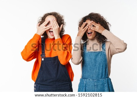 Image of joyful multinational women covering their eyes to each other Stock photo © deandrobot