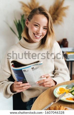 Fotografia radosny czytania magazyn śniadanie Zdjęcia stock © deandrobot