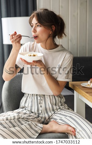 Photo of young caucasian woman eating granola while having breakfast Stock photo © deandrobot