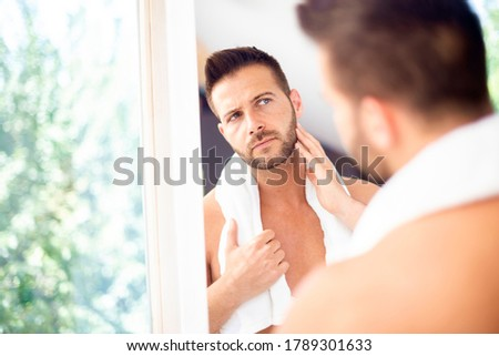 Man touching neck looking in mirror in home bathroom. Body care panoramic banner Stock photo © Maridav