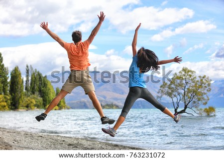 New Zealand tourists couple jumping of happiness at Wanaka Lone . Happy young people doing funny jum Stock photo © Maridav
