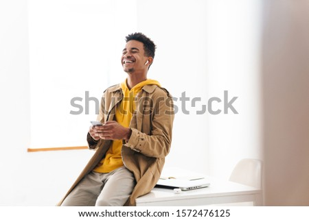 Photo of african american man using earpods while sitting on floor Stock photo © deandrobot