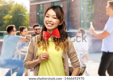 happy asian woman with bow tie over rooftop party Stock photo © dolgachov