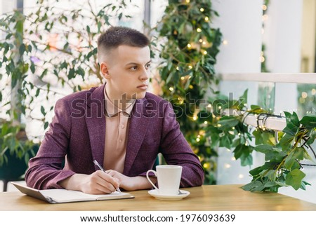 Businessman sitting indoors and writing plan in his diary. Blank stock photo © HASLOO