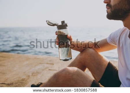 man drinking water from a bottle on the beach landscape stock photo © juniart