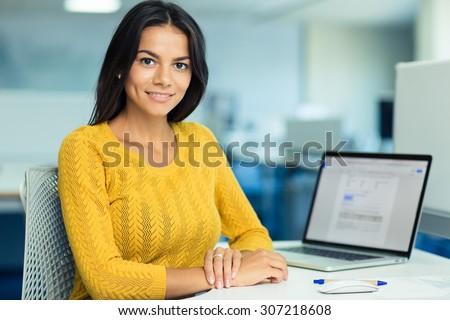 笑みを浮かべて · ビジネス女性 · 座って · 表 · 見える · カメラ - ストックフォト © hasloo