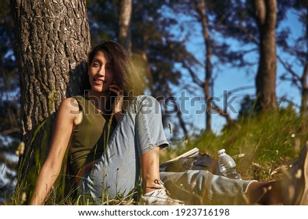 brunette with long hair sitting down with hands on her knees, le Stock photo © feedough