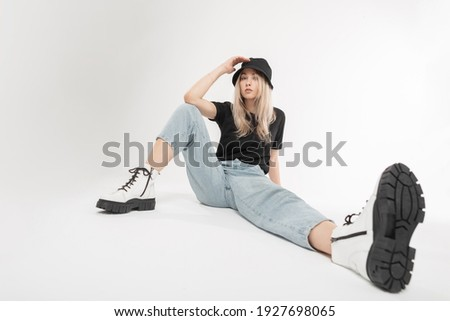 Girl in jeans, hat and white shirt sitting in white studio. Horizontal format. Stock photo © Paha_L