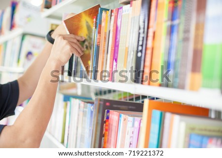 Handsome man choosing book from bookshelf for reading in evening Stock photo © deandrobot