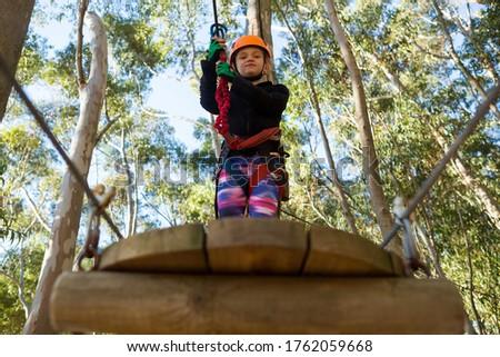 Little girl wearing helmet holding rope and standing on wooden platform Stock photo © wavebreak_media