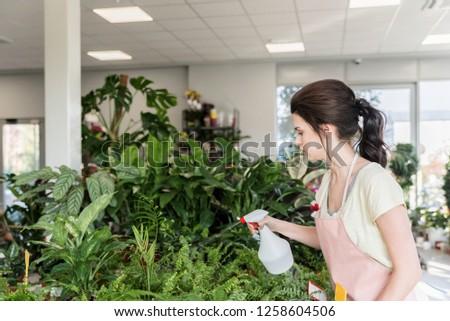 Stock photo: Woman gardener standing over plants in greenhouse water flowers