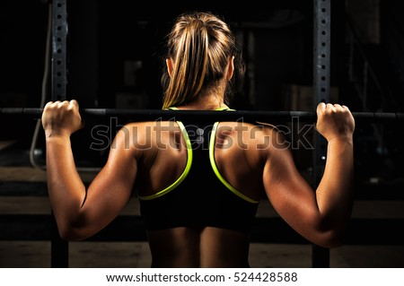 Concentrated sports woman doing exercise with barbell and looking away Stock photo © deandrobot