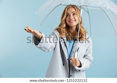 Image of lovely woman 20s wearing raincoat standing under transp Stock photo © deandrobot