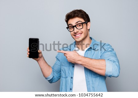 Handsome cheerful man holding smartphone and smiling to camera Stock photo © deandrobot