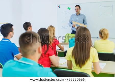 Rear view of schoolgirl studying in classroom sitting at desks in school Stock photo © wavebreak_media