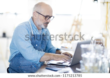 Creative artist concentrating on network while looking at laptop display Stock photo © pressmaster