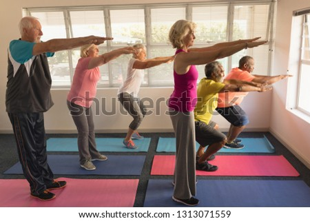 Side view of group of active senior people performing exercise on yoga mat at home Stock photo © wavebreak_media