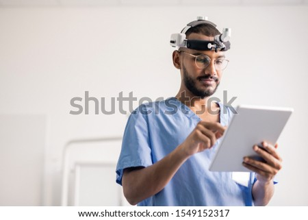 Young medical professional with touchpad scrolling through online data at work Stock photo © pressmaster