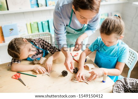 young woman helping one of schoolgirls with handmade xmas decorations at lesson stock photo © pressmaster