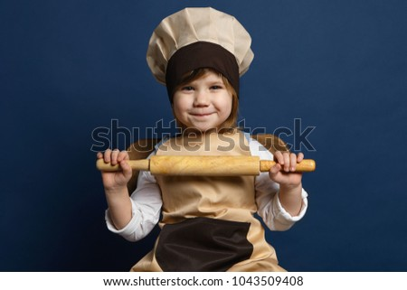Pretty young smiling chef in white uniform holding rolling-pin while cooking Stock photo © pressmaster
