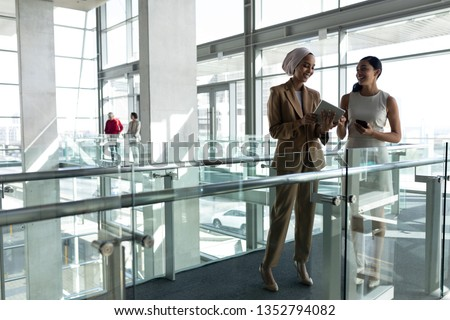 front view of two businesswoman laughing and discussing together on first floor walkway of the offi stock photo © wavebreak_media