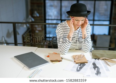Tired designer in casualwear trying to concentrate while thinking of new ideas Stock photo © pressmaster
