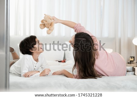 Dark haired young Caucasian lady with pleasant smile plays with pedigree dog, wears sweater, jeans a Stock photo © vkstudio