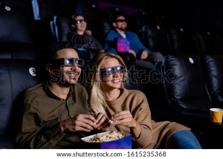 Cheerful couple in 3d eyeglasses eating popcorn while spending time in cinema Stock photo © pressmaster