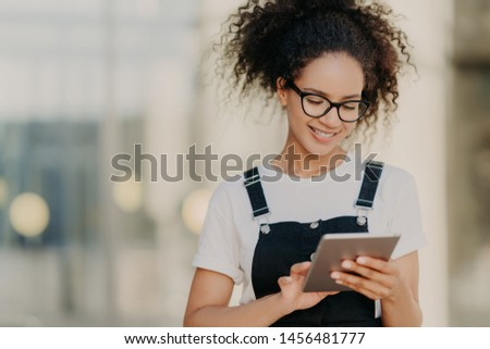 Photo of attractive millennial girl with crisp hair, holds digital tablet, surfes social networks, w Stock photo © vkstudio
